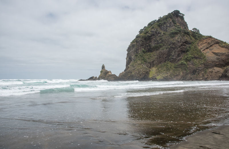 Stunning black sand Piha Beach with Lion Rock on an overcast day in Auckland, New Zealand Auckland Coastline Lion Rock Tasman Sea Travel Beach Black Sand Beach Famous Place Horizon Over Water Land Motion Nature New Zealand Piha Power In Nature Rock - Object Rock Formation Scenics - Nature Sea Shore Solid Stack Rock Volcanic Landscape Volcano Water