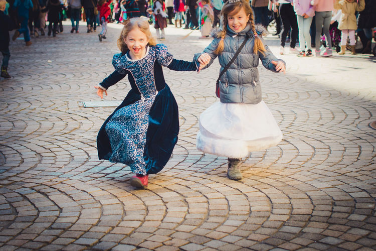 Carnival Happy Princess Sisters Tradition Childhood Cobblestone Costume Frienship Front View Full Length Girls Happiness Looking At Camera Outdoors Real People Smiling Street