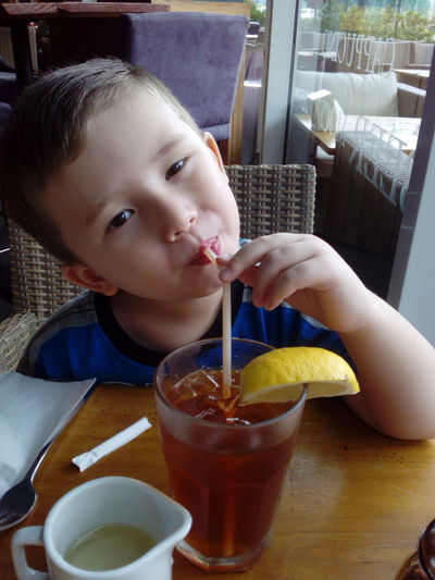 Portrait of cute boy sipping drink at restaurant