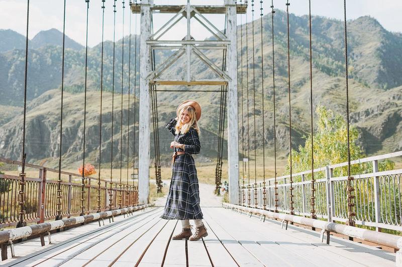 Happy young blonde woman in plaid dress on horochowski bridge on katun river, altai mountains