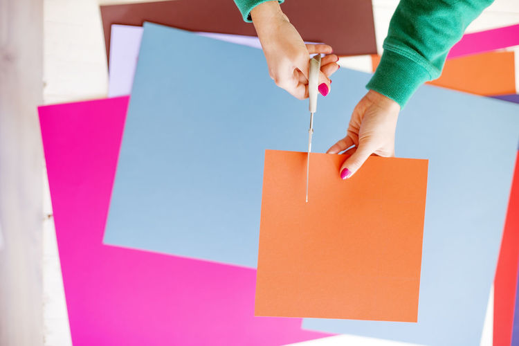 Cropped Hands Of Woman Cutting Orange Kraft Paper On Table