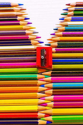 Close-up of sharpener on multi colored pencils over white background