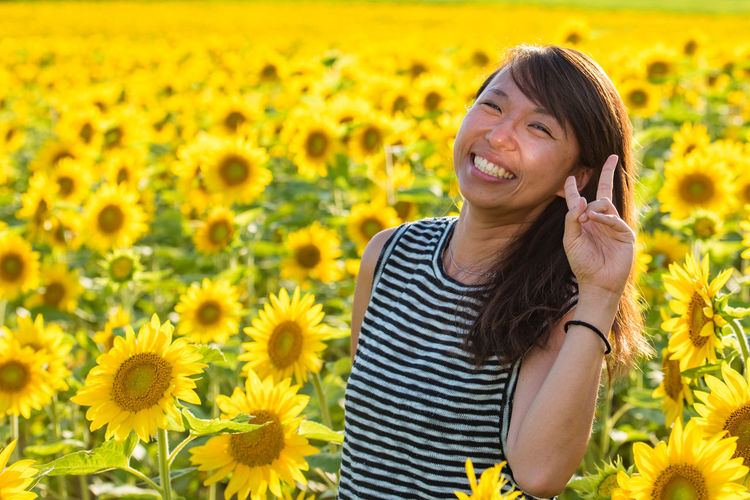 Portrait of a smiling young woman gesturing peace sign in sunflower field