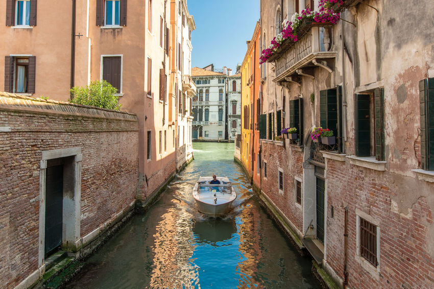 A boat on a canal in Venice Architecture Blue Sky Building Canal City Day Mode Of Transportation No People Outdoors Reflection Residential District Transportation Travel Travel Destinations Water Waterfront Window