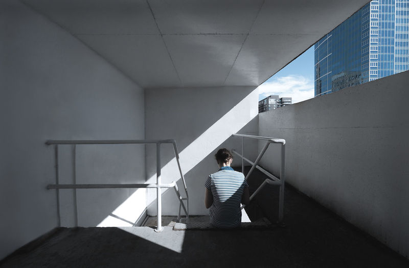 Rear view of woman sitting on staircase