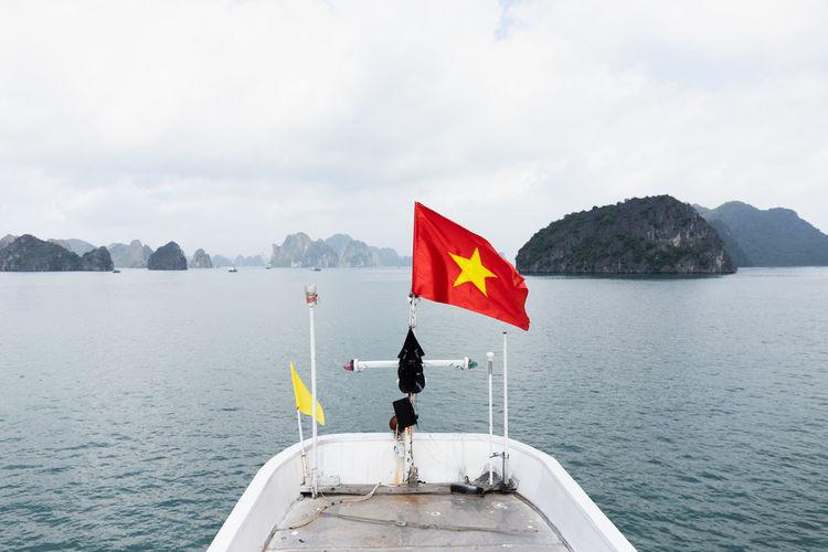 Flag sailing on sea against sky
