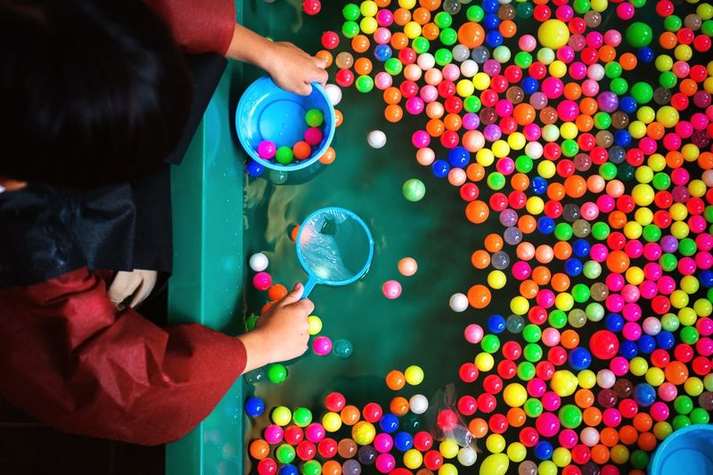 High angle view of boy collecting colorful balls floating in wading pool