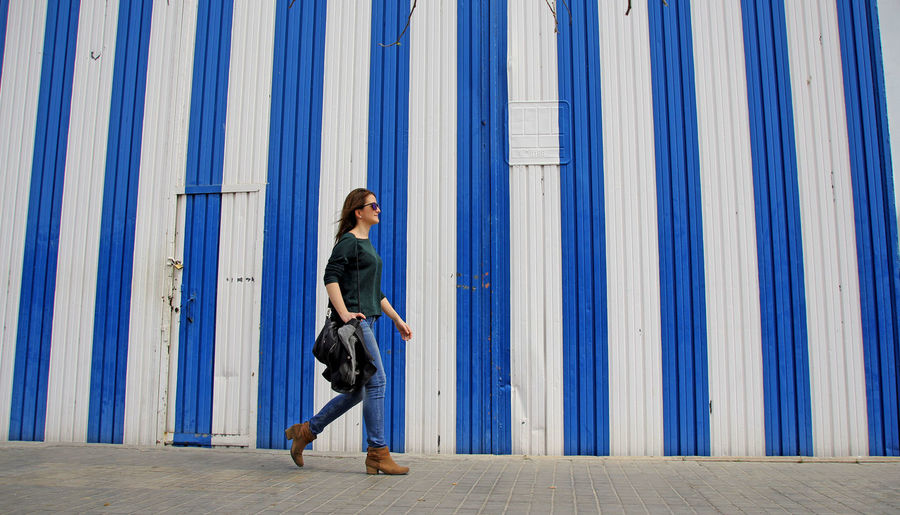 Woman walking by striped built structure