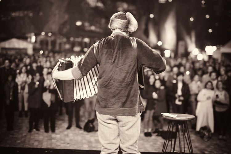 Rear View Of Man Playing Accordion In Front Of Audience