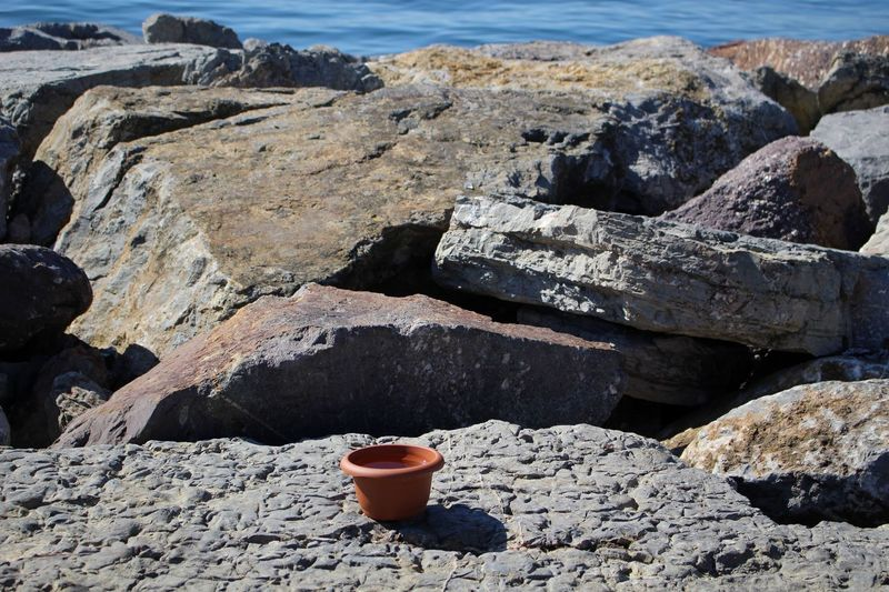 High angle view of empty flower pot on rocks by sea