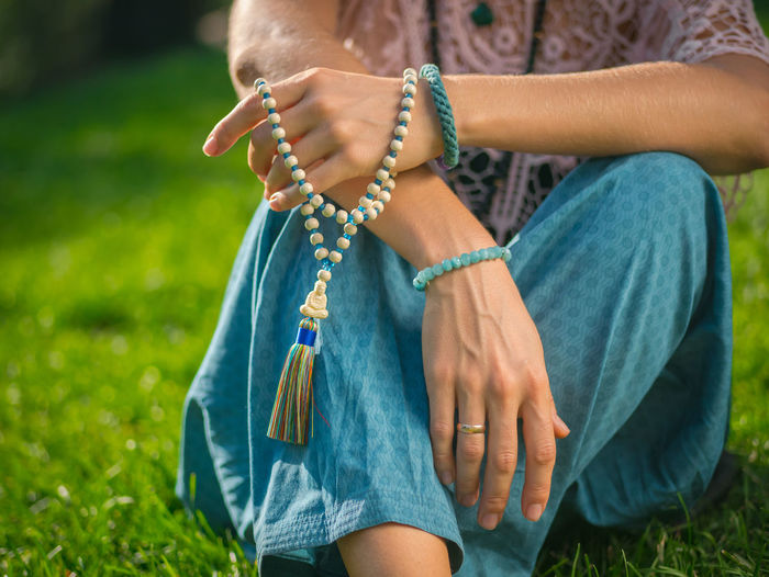 Midsection of woman with bead jewelry sitting on grassy field