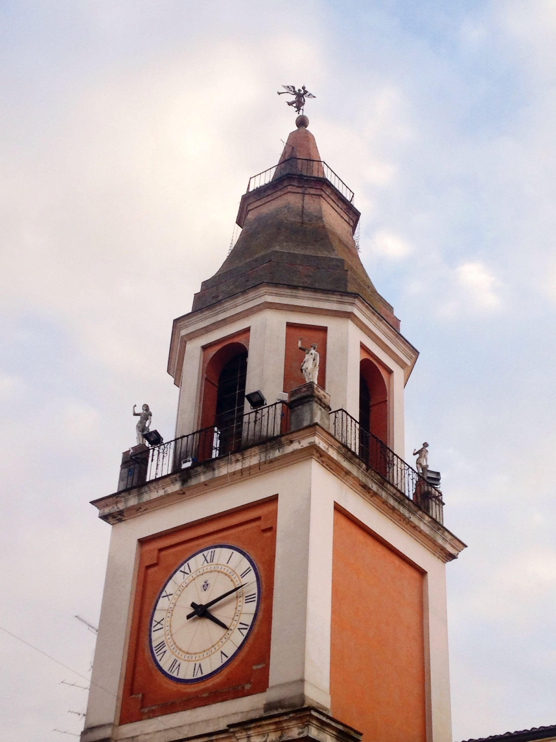low angle view, architecture, clock, religion, building exterior, built structure, clock tower, church, sky, place of worship, time, spirituality, cross, high section, cloud - sky, tower, cloud, cathedral