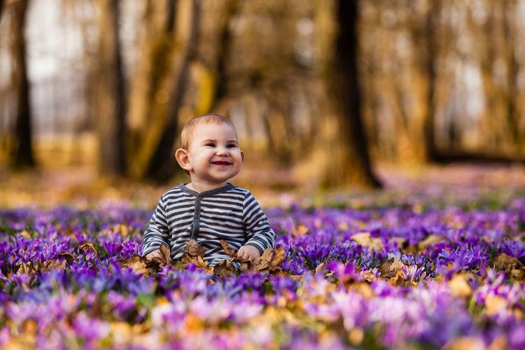 Portrait of smiling girl standing on purple flowering plants