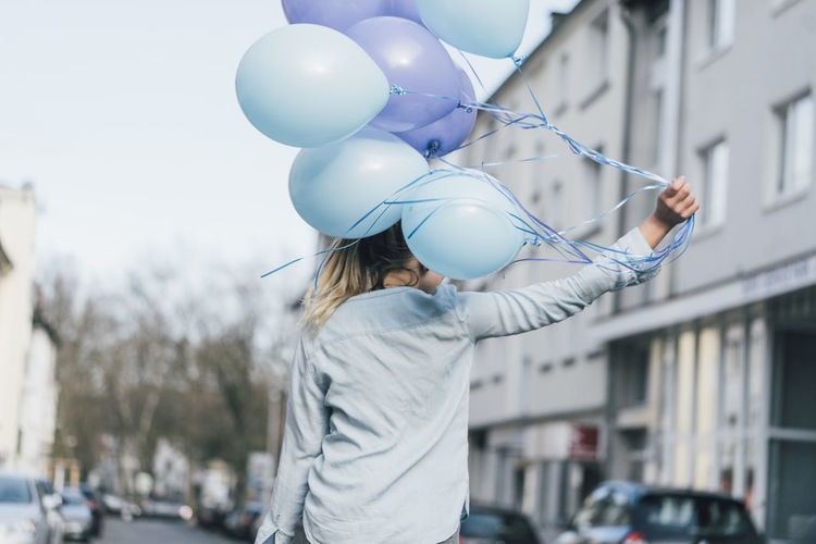 Midsection of woman holding balloons