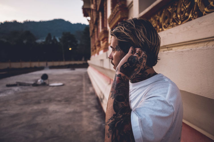 Man with tattoo looking away while standing by wall outdoors