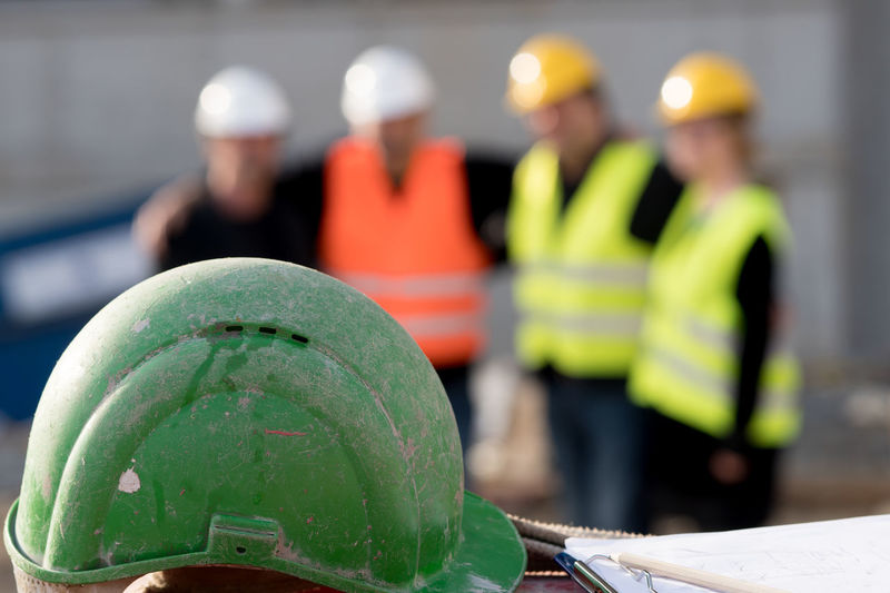 Close-up of hardhat against engineers at construction site