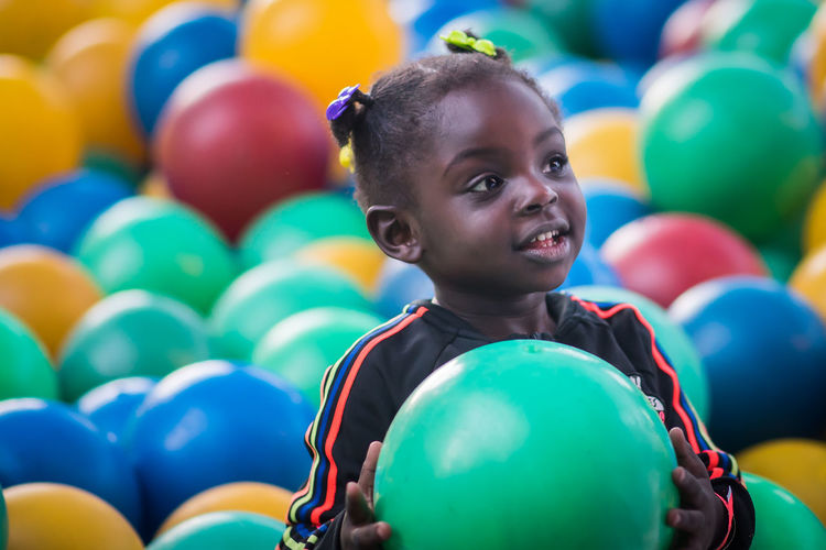 Close-Up Of Cute Girl Playing With Balls