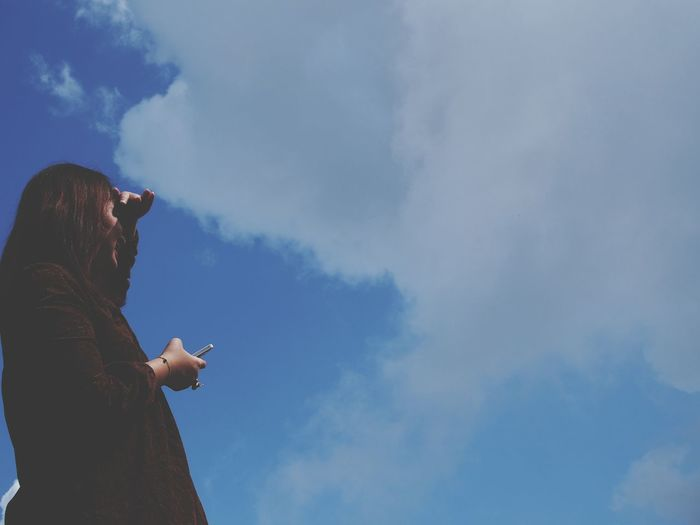 Low angle view of woman shielding eyes while standing against sky