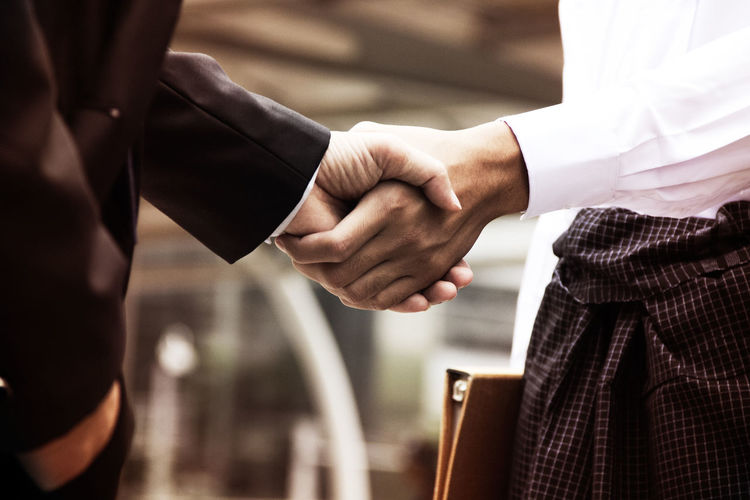 Midsection of business people giving handshake at office