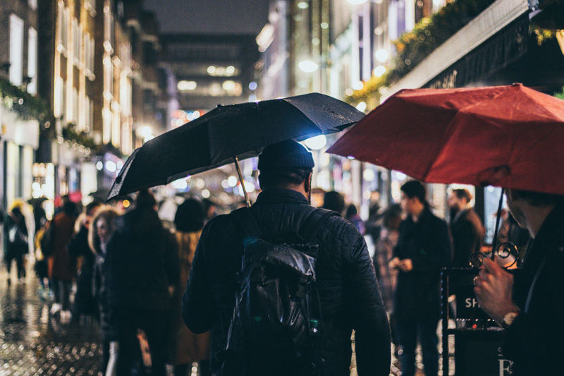 Rear view of people standing on street in rain