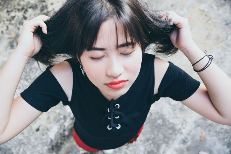 High angle of young woman with eyes closed standing on footpath
