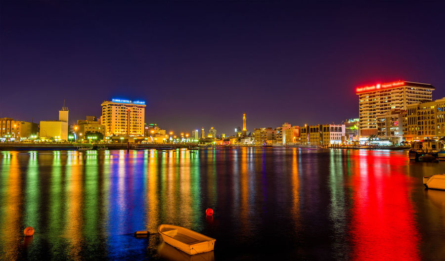 Illuminated buildings by river against clear sky at night