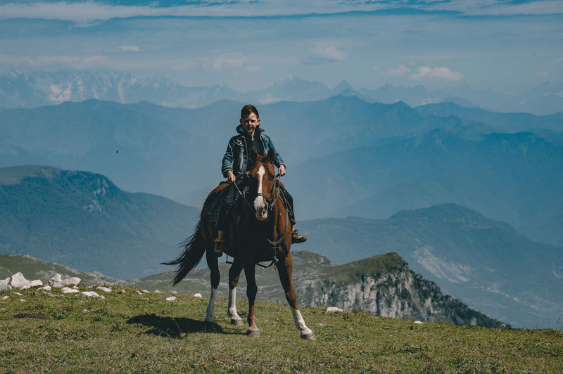 People riding horse on mountain against sky