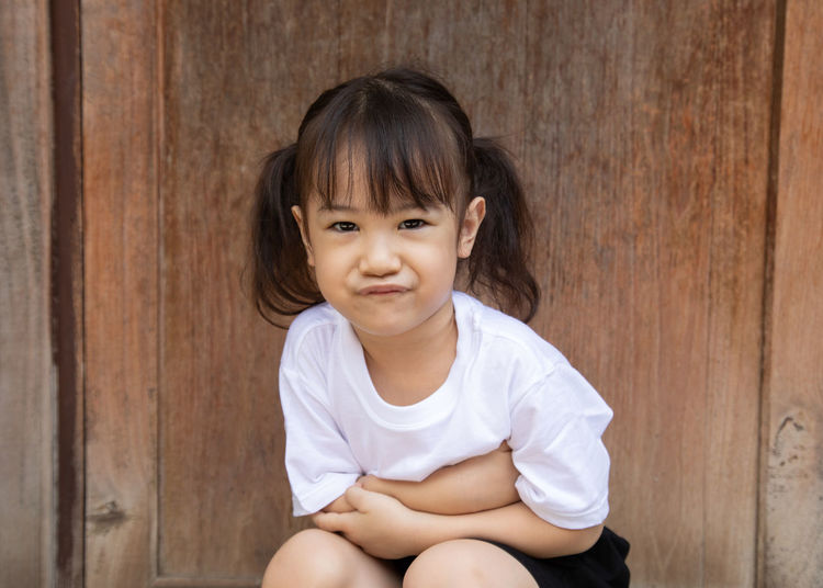 Portrait of girl crouching by wall