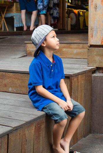 Full length of boy sitting on wooden steps