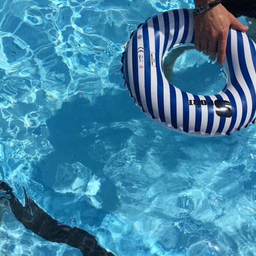 Human Hand Holding Rubber Ring In The Pool