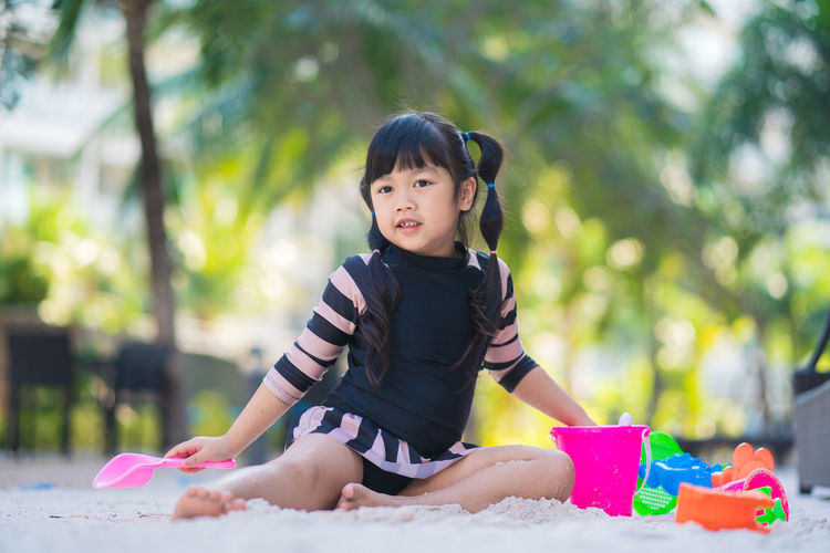 Cute girl sitting on toy while looking away outdoors