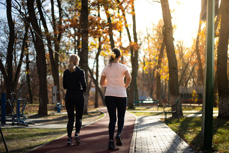 Rear view of women running on footpath in park