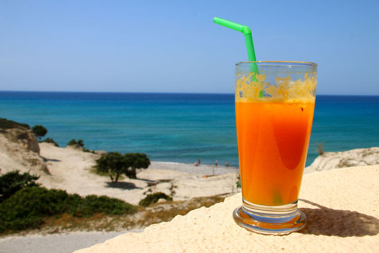 Drink on table at beach against blue sky