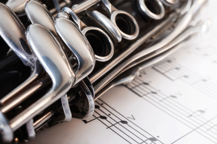 Close-up of clarinet on musical notes