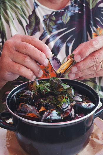 Close-up of hand holding mussels over container