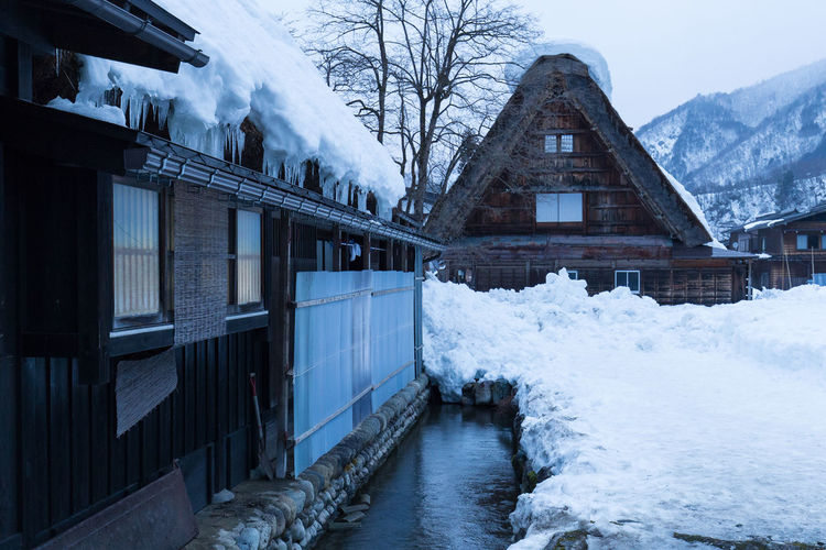 Snow covered houses by frozen lake against sky