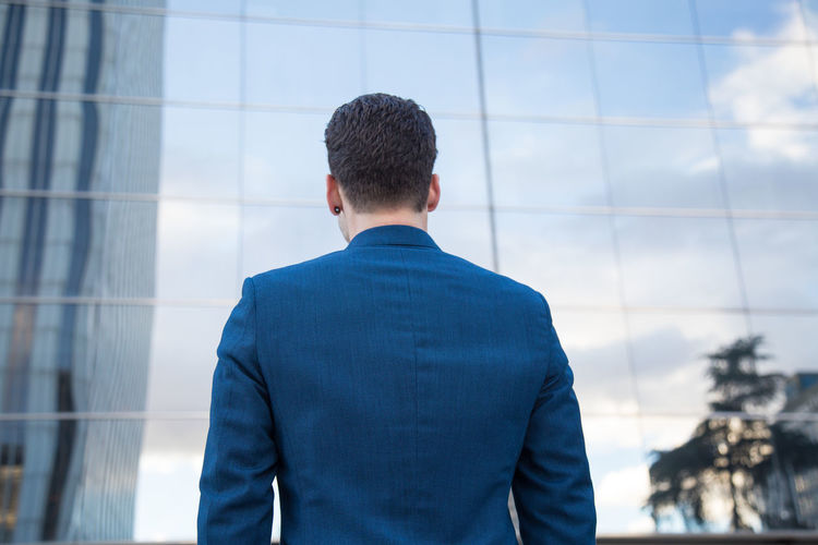 Rear View Of Businessman Standing Against Modern Building