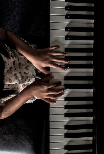 Midsection of girl playing grand piano
