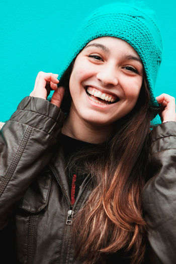 Close-up portrait of cheerful young woman wearing knit hat against turquoise background