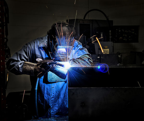 Welder welding metal in workshop