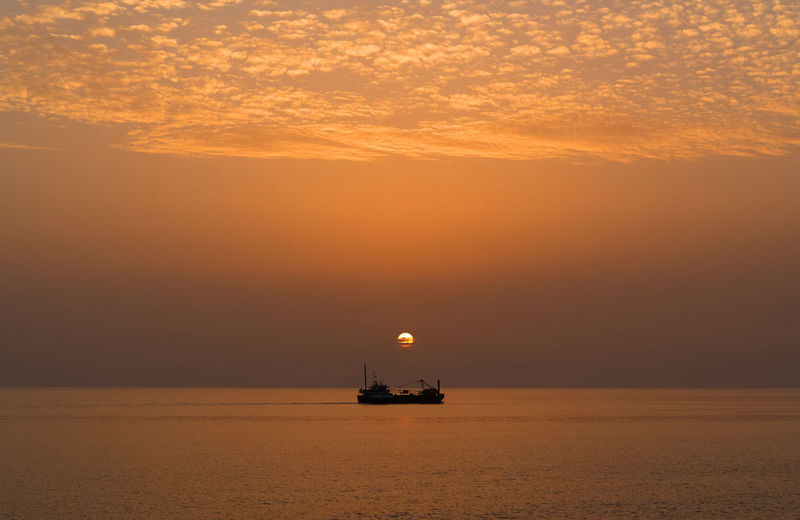 Scenic view of sea against orange sky with a boat