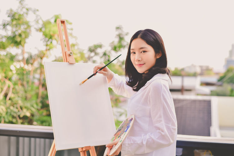 Portrait of woman painting on canvas against sky