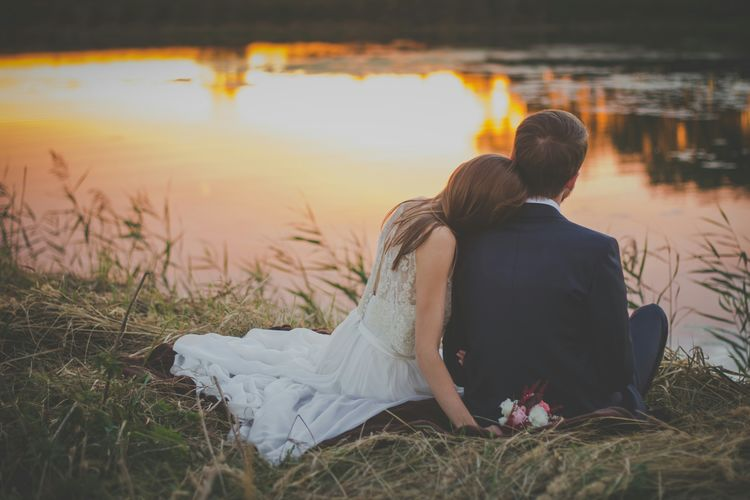 Rear View Of Wedding Couple Sitting By Lake During Sunset