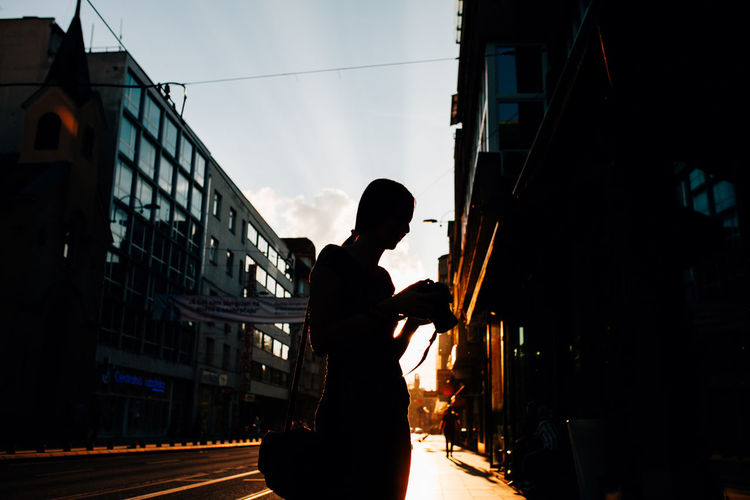 Silhouette of young woman photographer at the sunset photographing streets Streetphotography Young Women Girl Silhouette Golden Hour Portrait Close-up Sarajevo Autumn One Person Architecture Real People Outdoors Nature City Camera Photographer Photographing Looking At Camera Walking Traveler City Life
