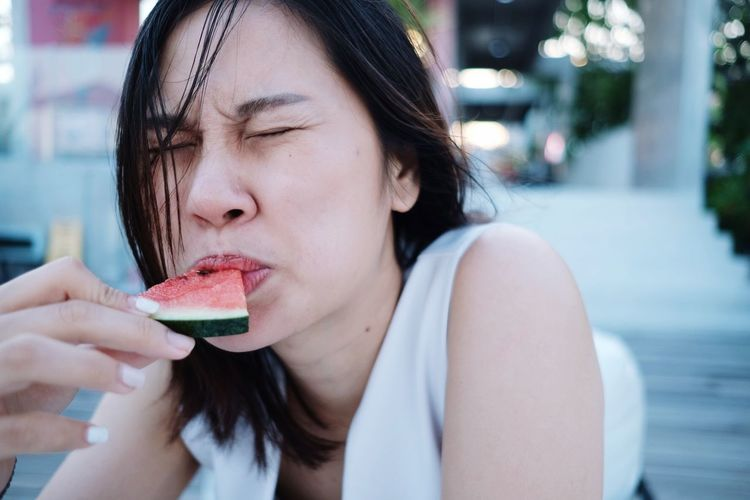 Close-up of woman eating watermelon slice
