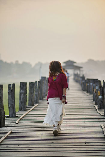 Woman walking on wooden walkway against sky