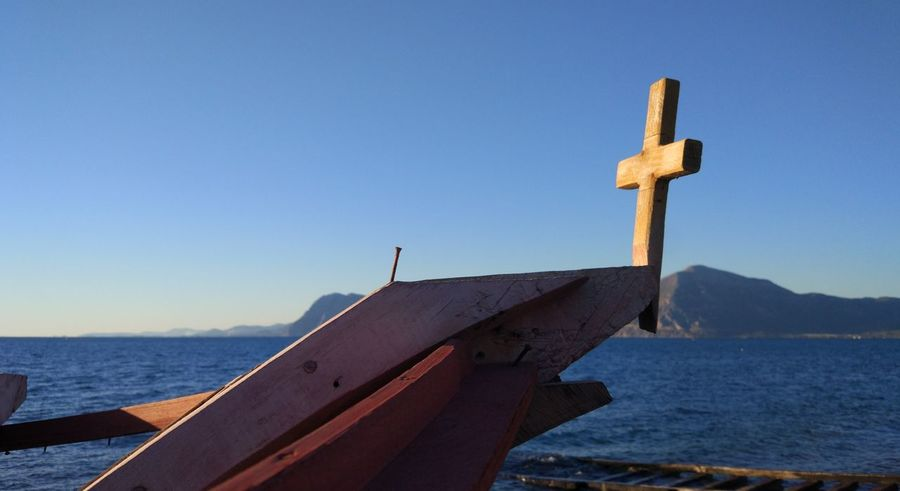 The nail and the cross Hull Beauty In Nature Blue Boatyard Built Structure Clear Sky Close-up Cross Day Fishing Boat Mountain Nail Nature Nautical Theme No People Outdoors Part Of A Ship Religion Religious  Scenics Sea Sky Water
