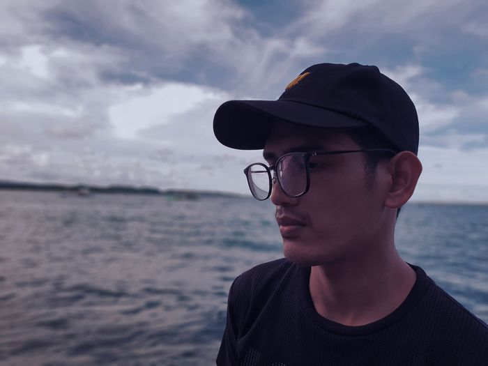 Thoughtful young man wearing eyeglasses looking away against sea and cloudy sky