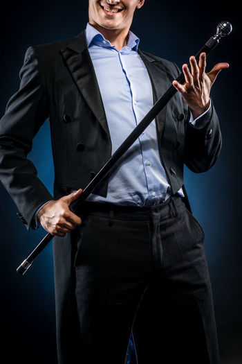 Midsection Of Man In Blazer Holding Cane While Standing Against Black Background