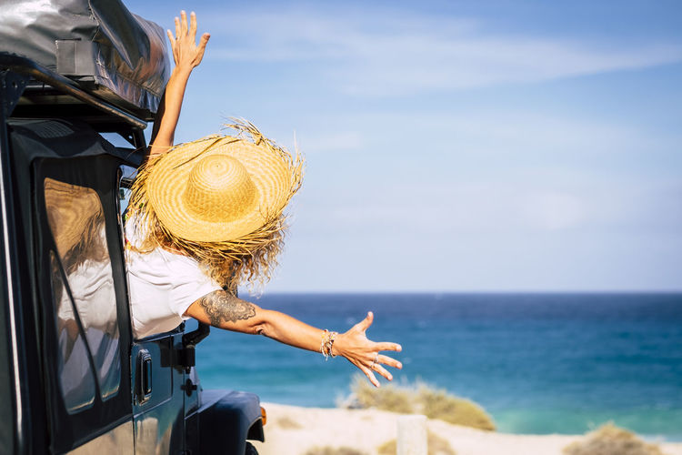 Rear view of excited woman looking at blue sea while sitting in car during sunny day
